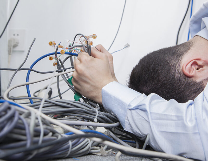 Frustrated man trying to figure out computer cables